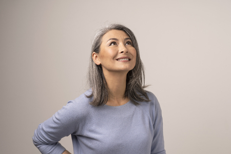 Smiling Woman With Grey Smiles And Looks Up. Attractive Middle-Aged Asian Woman Looking Up And Smiling. Studio. Portrait.
