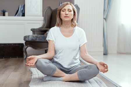 A Woman Takes Yoga at Home. Woman Over 50 Years Old. She Took the Pose of the Asana on the Floor. Closing Her Eyes She Meditates. Close Up Shot. Stock Photo