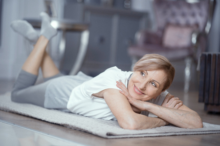 A Woman Over 50 Enjoys Relaxation After Yoga. She Lies on the Floor at Home. Woman Gently Smiles. Yoga Gives Her Pleasure. Close Up Shot.