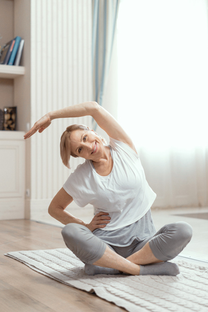 Woman Doing Yoga at Home. In Appearance a Woman is Over 50 Years Old. Yoga Helps Her to Keep Herself in Good Shape.