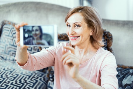 Elderly Woman at Home in the Living Room with a Phone in Her Hands. A Woman Wants to Take a Picture of Herself on the Phone. On the Face of the Womans Sweet Smile. Close Up Shot.