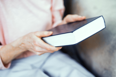 Blue Book in the Hands of An Elderly Woman. The Woman Took the Book to Read it. Close Up Shot.