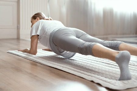 Middle Aged Woman In Sportwear Doing Plank Position On Yoga Mat .Healthy Lifestyle. Yoga Practice Concept.