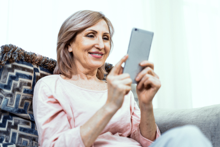 Woman of European Appearance at Home on the Couch with a Phone in Her Hands. In Appearance Woman are Over 50 Years Old. In the Phone She Reviews the Photos and Smiles. Imagens