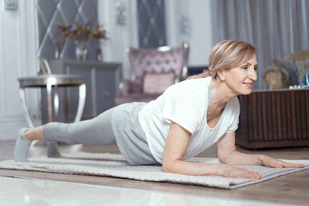 Yoga Exercise At Home. Middle Aged Woman Making Plank Position. Yoga Practice Concept. Healthy Lifestyle. Stock Photo