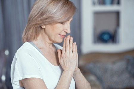 Middle Aged Woman Meditating Yoga At Home. Puts Hands Together. Relaxing. Yoga Concept. Stock Photo