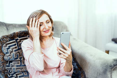 Adult Woman Resting at Home in the Living Room. She Has a Phone in Her Hands. She Gently Smiles and Wants to Take a Photo. Imagens