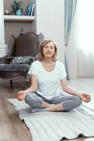 Middle Aged Woman Sitting On The Floor On Yoga Mat In Lotus Position. Making Mudra Gesture. Yoga Concept.