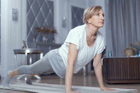 Active Middle Aged Woman In Sport Uniform Making Plank Position On Yoga Mat. Yoga Practice Concept. Stock Photo