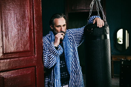 Thoughtful Man Smokes Leaning On The Door And The Punching Bag. Attractive Bearded Man Touches The Punching Bag And Smokes Pensively Looking Down Stockfoto