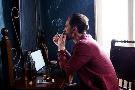 Stylish Bloger Brutal Appearance Sits at Home at His Desk. On the Table He Has a Laptop and An Alcoholic Drink. A Man Inventing New Articles Smokes a Cigarette.