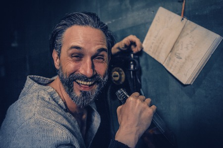 Handsome Man Laughs At Camera While Holding A Bottle Of Whiskey. Drunken Bearded Man s Hand Rests On The Rotary Phone As He Laughs Out Loud And Drinks. Blurred Image Of A Notebook Hanging On The Wall Near The Rotary Phone. Portrait. Banco de Imagens