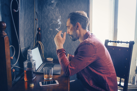 Concentrated Bearded Man Holds A Cigarette While Working On Laptop. Handsome Guy Holds A Cigarette Smoking. Bottle Of Whiskey, Smartphone And Opened Laptop Are On The Wooden Table With A Mirror. Side-View. Profile. Bohemian Lifestyle. Bluish Coloring Banco de Imagens