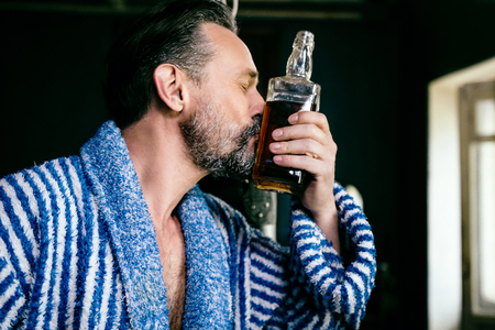 Handsome Brutal Man Likes to Drink. A Man Who Looks About 40 Years Old. In His Hand is a Bottle of His Favorite Whiskey Which He Kisses. The Wan is Wearing a Bathrobe.