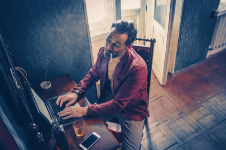 Busy Bearded Man With A Cigarette In His Mouth Types On The Laptop. Careless Middle-Aged Programmer Smokes And Drinks While Working From Home. Top View Banco de Imagens
