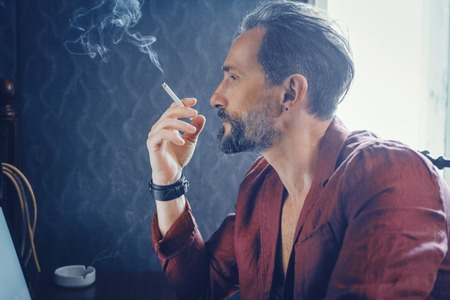 Close Up Profile of a Man With a Beard. The Appearance of a Man Tooks Brutal. Stylish Man Smoking a Cigarette With a Serious Face. Banco de Imagens
