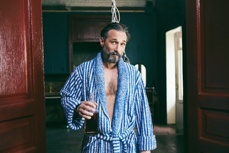 Handsome Brutal Man With a Beard Loving Drinking Alcohol. In His Hand is a Bottle of His Favorite Whiskey. The Man is Wearing a Blue Bathrobe.