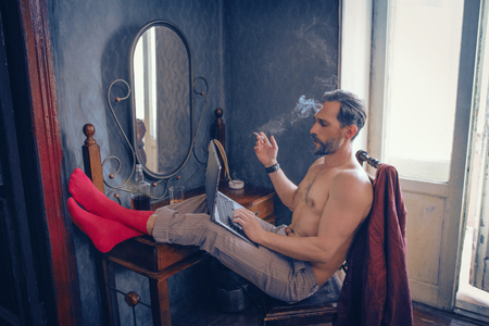 Half-Naked Guy Puts His Legs In Red Socks On The Table While Typing On The Laptop And Smoking.