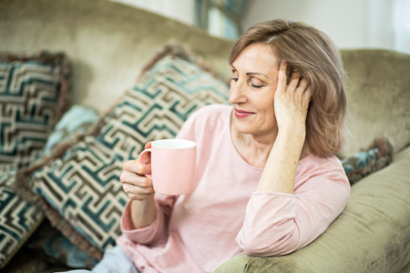 Attractive Middle Aged Woman With Closed Eyes Sitting On Sofa. Relaxing After Yoga. Home Relax Concept.