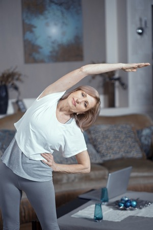 Middle-Aged Woman In Sport Cloth Is Holding One Hand On The Hip And Bends To The Side Stretching Her Other Hand. Yoga Poses For Beginner. Vertical Shot