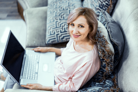 Charming Mature Woman Works From Home. Smiling Woman With A Laptop On Her Knees Looks At Camera. Top View.