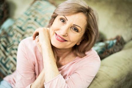 Donna di aspetto europeo che riposa a casa nel soggiorno. In apparenza la donna ha più di 50 anni. La donna sorride delicatamente nel telaio. Colpo ravvicinato.