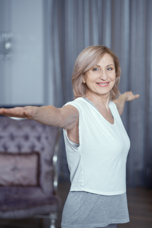 Smiling Woman Stretches Her Arms To The Sides. Happy Middle-Aged Woman Does Standing Yoga Poses. Healthy Lifestyle