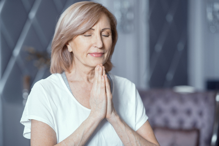 Peaceful Woman With Closed Eyes Does Namaste With Prayer Hands. Charming Woman Holds Her Palms Pressed Together Praying. Portrait.