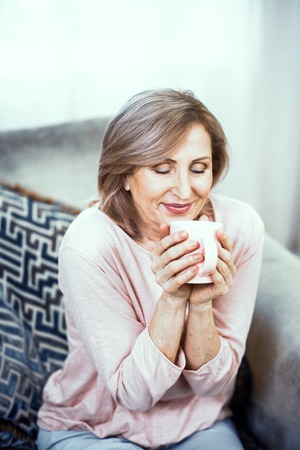 Attractive Mature Woman Sitting On Sofa And Having Coffee. Relaxing After Yoga. Relaxing At Home Concept.