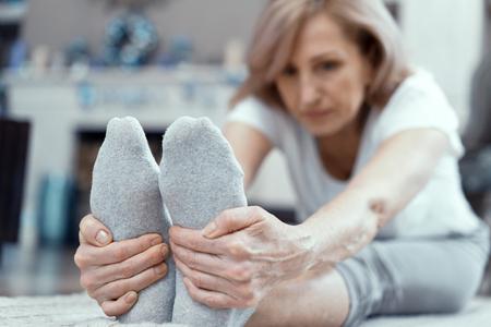 Mujer concetrada estira sus pies tocándose los pies. Mujer madura hace ejercicio de yoga para alcanzar los dedos de los pies. Estilo de vida saludable. Extensión. Foto de archivo