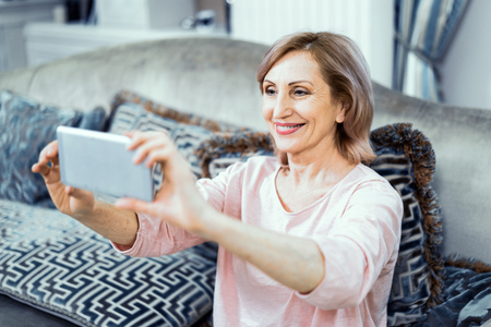 Happy Woman Takes Phone With Front Camera With Her Phone. Mature Woman Photographs Herself Sitting On A Sofa. Selfie Concept