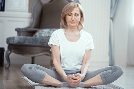 Beautiful Woman Sits With Crossed Legs On The Mat Practicing Yoga. Calm Mature Woman Stretches Her Legs. Fitness Concept
