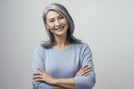 Jolie femme asiatique mature aux cheveux gris et optimiste sourit largement en studio et croise les mains, la tête inclinée. Mains Et épaules Tonifiées Portrait Sur Fond Blanc. Banque d'images
