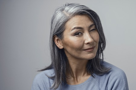 Beautiful Asian Grey-Haired Women with Natural Make-up and Cheekbones Closes Eye Kindly in Head Tilt. She Wears Blue Sweater. Closed-Up Portrait in Studio.