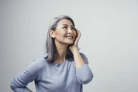 Peinado gris de mujer de mediana edad sexy en Sudio. Ella toca su mejilla y levanta los ojos soñando. Foto de estudio de media vuelta.