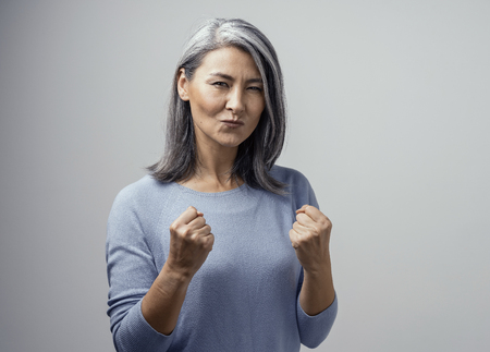 Happy Mature Asian Female Model Smiles Happily. She Celebrates Victory and Holds Fists in Satisfaction. Hand Photo in Studio on White Background Archivio Fotografico