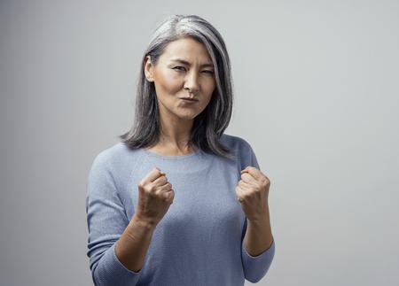 Modelo femenino asiático maduro feliz sonríe felizmente. Celebra la victoria y sostiene los puños satisfecha. Foto de mano en estudio sobre fondo blanco. Foto de archivo