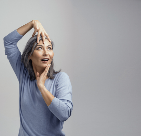 Beautiful Female Model Posing For The Camera. Charming Middle-Aged Asian Woman Touching Her Face With Hands and Looks Up in Surprise While Posing At The Photo Studio. Right Side Shot