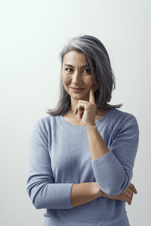 Smiling Asian Woman With Grey Hair Stands And Touches Her Cheek With Pointing Finger. Another Hand is On Chest. Charming Middle-Aged Lady In Casual Cloth Slightly Smiles And Props Her Head On Her Hand. Vertical Portrait.