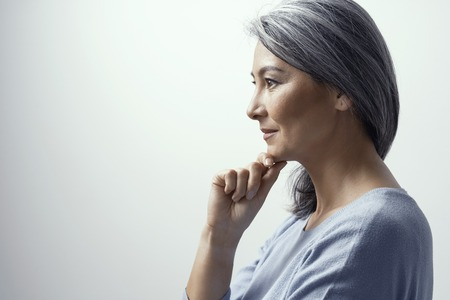 Asian Middle-Aged Woman Profile. Beautiful Woman with Grey Hair Stands on a White Background in Studio Slightly Smiling and Touches her Chin. She is Thinking Meditatively. Tonned Portrait.