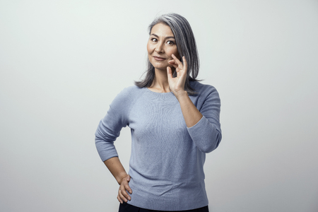 Asian Dreamy Mature Woman Posing Coquettishly a White Background in Studio and Smiles Putting Hand to Face. She Wears Blue Sweater. Horizontal Portrait in Cold Shades Stock Photo