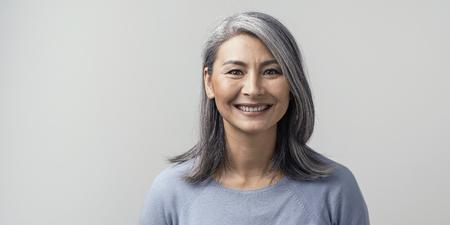 La bella donna asiatica matura sorride ampiamente in studio. Ritratto chiuso tonificato lato destro. Sfondo bianco.