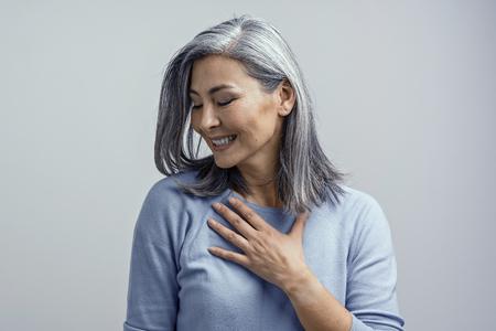 Hermosa mujer madura asiática de pelo gris se toca el pecho con gratitud y sonríe coquetamente de emoción. Ella está medio vuelta a la cámara. Foto de estudio tonificada. Foto de archivo