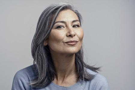 Gorgeous Atrractive Korean Woman with Gray Wavy Hair and Cheekbones Smiles Gently to Camera. Closed-Up Tilted Head and Shoulders Toned Studio Portrait.