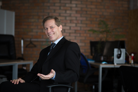 Smiling Businessman Hodling Hand While Sitting On Chair In Modern Office. Wearing Suit. Business Concept.