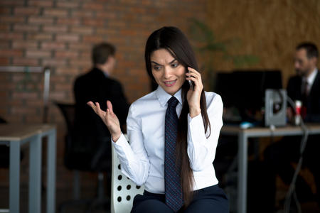 Businesswoman Speaking Over Telephone In Office. Wearing White Blouse And Tie. Business Concept.