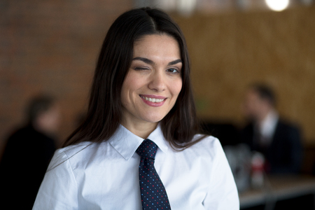 Cheerful smiling winking businesswoman in a white blouse and a black tie. She is standing in the office.Two colleguaes are working behind her.