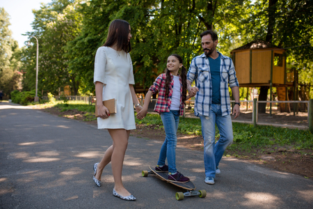 Happy Young Family Having Active Time In Summer Park. Girl Skateboarding. Happy Family Concept. Фото со стока