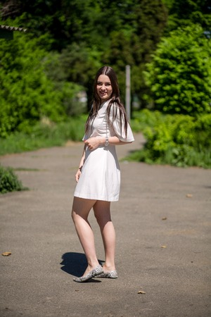 Nice Brunette Woman In Beige Summer Dress Standing On Park Path. Green Trees On Background.Beauty Concept. Фото со стока