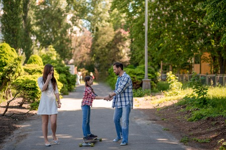 Young Daughter Standing On Skateboard On Park Path. Beautiful Mom In Summer Dress And Father In Casual Clothes Near.
